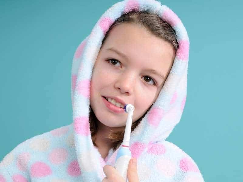 Young girl with an electric toothbrush