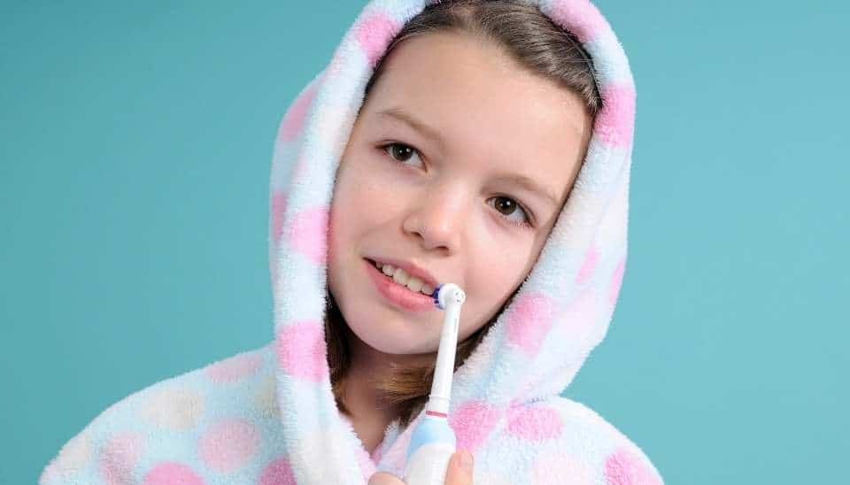 Young girl holding an electric toothbrush